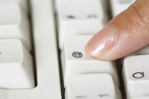 Finger pushing a key on a keyboard