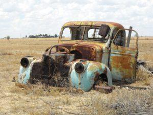 old, junky car in a field